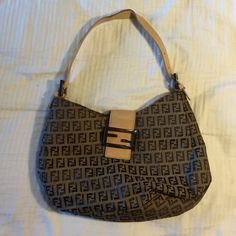 FENDI Borsa Hobo Bag This bag has been the love of my life for the past few years, but it's time to let go. The handle is real leather and separated, as shown, from use. Fabric in great shape, no stains. Inside has open sides and zippered center pouch. Buckle strap is a magnetized closure. Enough strap room to put over your shoulder. Purchased at the NYC display. FENDI Bags Hobos
