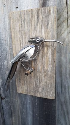 Bird made from recycled stainless steel spoons and forks.