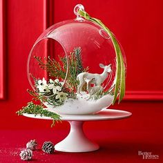 Create a winter wonderland inside a clear glass bulb terrarium. Start with a base of faux snow and tuck in a miniature house and small branches (available at crafts stores). Place you terrarium on a footed cake stand in the center of the table for an easy yet festive table decoration./