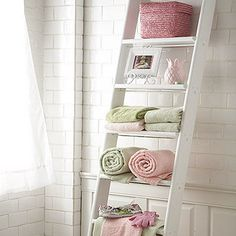 White ladder used to display color coordinated towels and bath accessories. Great for a tiny bathroom.  More bathroom organization ideas http://thegardeningcook.com/bathroom-organization-ideas/