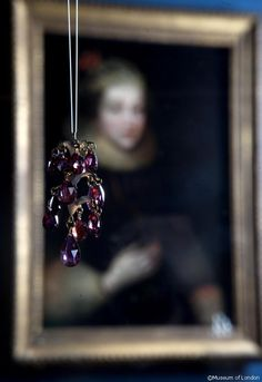 Garnet Pendant at the Cheapside Hoard Exhibition, Museum of London. Portrait behind is Elizabeth Vernon, Countess of Southampton, who wears a similar pair. Pendant Jewelry, Jewelry Necklaces, Jewellery Box, Jewellery Display, Beaded Jewelry, Jewellery Exhibition, Renaissance Jewelry, Garnet Pendant, London Museums