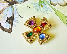 Jeweled Gold Tone Maltese Cross Brooch, 80's Colorful Cabochons and Faceted Rhinestone Pin by dazzledbyvintage on Etsy https://www.etsy.com/listing/276686544/jeweled-gold-tone-maltese-cross-brooch