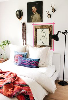 Eclectic bedroom with an art wall and accent pillows