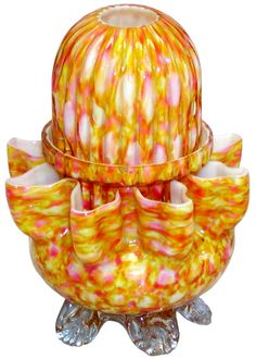 Pyramid-size yellow, pink & white glossy end-of-day glass dome with embossed ribs & 2 ground air vents in its bottom rim, resting in a matching lamp cup. The lamp cup rests on the square-crimped 8-pointed rim of a matching base that has 5 applied clear tooled feet / http://www.fairy-lamp.com/Fairylamp/FairyLampUndoc321340.html
