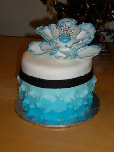 This was my first attempt to make a petal cake. It was fun and can't wait to try again. This is a cosmo cake, with fresh strawberries in the cake and between layers. Covered in fondant, the fantasy flowers is gumpaste with a blue sapphire edge and middle, and pearl stems. TFL :)