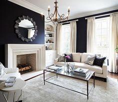 salon noir et blanc cosy et chic avec miroir rond esprit art déco au-dessus de la cheminée