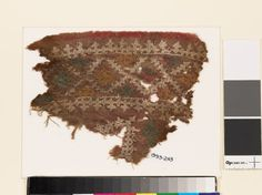 Textile fragment with diamond-shapes and crossesfront | Near East 10th-15th century | cotton, dyed red, and embroidered with white flax and yellow and blue-green silk; linen backing; with remains of stitching in blue thread, possibly cotton