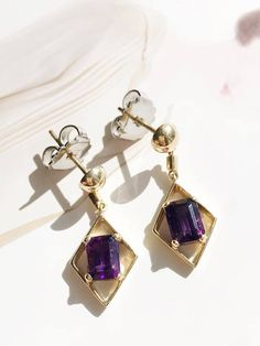 Royalty has always been associated with the deep purple color of these amethysts - so regal, beautiful and among the most desirable of the shades of this gemstone. The emerald cut brings out the vivid hue, and offers a geometric effect - a rectangular stone within a diamond shaped setting. These would make a wonderful bridal earring (or earring for those obsessed with The Crown!!)  HISTORY: Modern estate jewelry, circa 1980s  MATERIALS: 14k gold, amethysts, platinum backings  SIZE: The…