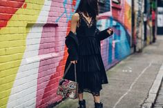 Anisa Sojka styles black H&M layered lace midi dress | Off the shoulder Malene Birger coat | Flat Zara boots with silver buckle | Gucci Dionysus GG Supreme canvas shoulder bag with bird, bee and floral embroidery | Baublebar choker necklace and leaf dimante earrings | Brunette straight shoulder length hair | Fashion blogger street style shot in Shoreditch, London in front of colourful graffiti art walls by Moeez Ali