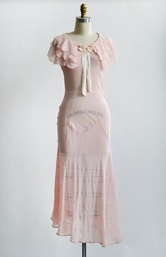 1930s sheer petal pink bias cut gown with sweet layered cape style sleeves with soft scallops. This sweet as can be vintage 30s dress has bow detail at neckline and pretty seam detailing along the skirt. Dress has slight asymmetrical hemline and will move beautifully as you dance and glide across the floor.