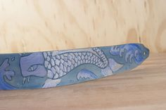 Large koi fish in dance in the water on the handmade leather Old Koi Guitar Strap.  The soft colors and flowing movements give this strap a wonderfully serene look.  This strap comes in two styles to work with both acoustic and electric guitars (as well as your banjo, bass or dobro!).