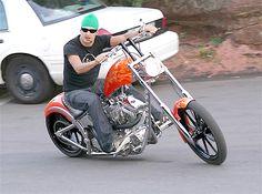 Kid Rock smokes a cigar while riding a chopper.