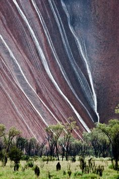 Water cascades down an Uluru rock face.   Uluru, also referred to as Ayers Rock, is a large sandstone rock formation in the southern part of the Northern Territory, central Australia. Photo by:  Peter Carroll