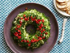 Holiday Cheeseball Wreath : Bring your outdoor holiday wreath inside with this festive and easy cheeseball. Use a small Bundt pan to form a wreath shape, or roll the mixture into a ball or log. For a cheeseball worthy of any big gathering, skip the Bundt pan and colorful garnish and roll the ball in toasted sliced almonds instead.