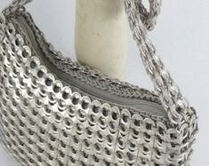 Recycling never looked so good! This handbag is made from post-consumer recycled, clean aluminum beverage can tabs and light gray nylon yarn. Soda Tab Crafts, Can Tab Crafts, Pop Tab Purse, Plastic Bottle Tops, Rock Vintage, Pop Can Tabs, Pipe Cleaner Crafts, Pipe Cleaners, Soda Tabs