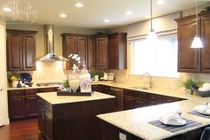 dark brown cabinets with light granite countertops in kitchen like the hood  pendant lights  light counter