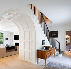 Paneled doors are hidden in the curve of the arched opening in the foyer, providing extra storage and creating a seamless appearance when closed.