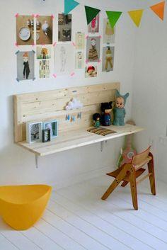 Salita infantil con un escritorio de madera, en su color natural, adosado a la pared y sin patas.