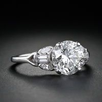 1.98 Carat Diamond Estate Engagement Ring    Art Deco  A glorious bright white transitional-cut diamond weighing 1.98 carats is tastefully presented in this distinctive platinum and diamond setting which dates back to the 1930s. The beautiful diamond is flanked on both sides with an arrangement of two old-cut marquise diamonds flaring outward from a straight baguette diamond which, in turn, transitions to an open triangle at the top of the ring shank. Price $18750 ★★★★★