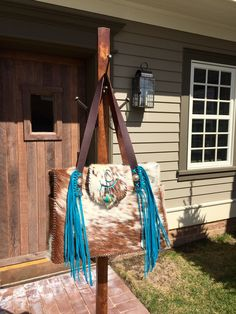 The Buckaroo Diaper Tote, with exterior pockets lined in suede and the owners brand and fringe in turquoise. From gowestdesigns.us