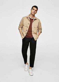 Wear a tan shirt jacket with black chinos to achieve a neat and sophisticated look. White leather low top sneakers will add a laid-back touch to an otherwise classic look.