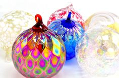 Cluster of colorful and festive glass ornaments all of which are hand crafted in the United States.