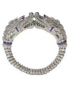 CHIMERA BANGLE | Cartier Paris, special order, 1929 | The first of its kind to be set entirely with gems | Platinum, pear-shaped diamonds, round old-, single- and French-cut diamonds, sapphire cabochons, buff-top sapphires and emeralds, gadrooned rock crystal (throat).