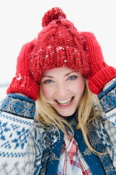 Gal in a red knit hat and mittens having outdoor winter fun.