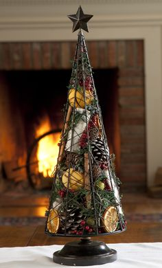 Holiday Spice Tree - A simple wire tree, filled to the top with pine cones, preserved juniper sprigs, juniper and canella berries, birchwood, cinnamon sticks, and dried orange potpourri. Gently scented with fragrant oil (fi r balsam, spruce needle, cedar, blood orange) blended with cinnamon, clove, amber, and a hint of vanilla; refresher oil included. Tree rests on a wood base topped with a metal star.