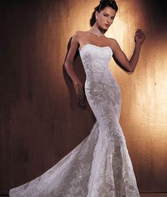 Lace over net wedding gown with trumpet skirt and a strapless, sweetheart neckline. This bridal dress has an attached train.