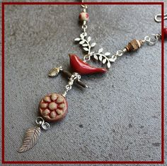 Ceramic handmade beads by Elaine Ray and Suburban Girl Studio and Kylie Parry ceramic red bird. Karen Hill Tribe silver lady bug. Bird is perched on Wood beads and hanging from that is a Suburban Girl