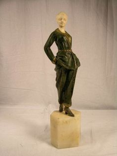 "GORI BRONZE AND IVORY FIGURE. SIGNED ""GORI FRANCE: FORTUNANTO GORI BORN ITALY, WORKED FREANCE 1895-1925).ART DECO COLD PATINATED FIGURE OF A WOMAN STANDING WITH HER HANDS IN HER POCKETS. MOUNTED ON A WHITE MARBLE BASE. SIGNED ""GORI FRANCE"" IN THE MARBLE. HEIGHT OF FIGURE 9 M1/2"". OVERALL HEIGHT 12 1/2""."