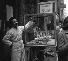 historicaltimes:  A shop boy selling pizza at a street market in Naples, Italy, in 1953 via reddit