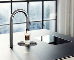 The TopBrewer by Scanomat is an automatic coffee making machine that dispenses coffee drinks from a faucet-like tap. The rest of the machine is hidden out of view in a cabinet-style enclosure. The TopBrewer can be controlled with an iPhone, iPad, or with the in-counter touchscreen.