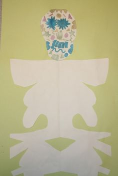 """Day of the Dead art project.  Fold paper in half lengthways, and write your name along the seam.  Fold in half and cut out, so you have the name with its mirror image to make the """"skeleton.""""  Add skull and decorate."""