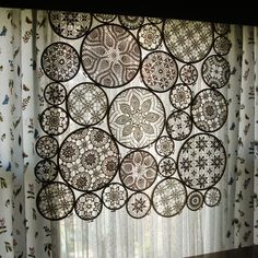 Doilies mounted in embroidery hoops; [This is stunning. I'd like to use individual hoops as wall decor and even with pink/purple doilies behind my bed. I'm bedbound and have large mirrored wardrobes for our kiddy pics so I'd see the wall art as often as I wished! ;) Mo]