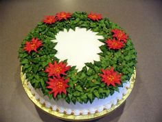 Christmas Wreath '06 - Chocolate cake w/cherry filling, vanilla buttercream frosting. Poinsettias are RI and dusted with gold pearl (hard to tell in photo). Gold pearls are fondant.