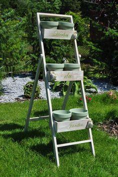 Duży, drewniany kwietnik ogrodowy z kolekcji Herbs de Jardin. Formą przypomina drabinę z trzema stopniami – skrzynkami, w których znajdują się ceramiczne doniczki. Na drewnianej konstrukcji widoczne białe przemalowania. Doniczki w kolorze jasnozielonym. Dodatkowym elementem dekoracyjnym są przyklejone na skrzynkach woreczki.  Kompozycja w stylu rustykalnym. Świetnie sprawdzi się w aranżacji ogrodu, tarasu, a także balkonu. Kwietnik nie tylko uporządkuje rośliny, ale także ...