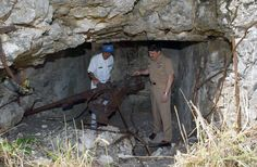 US Navy Master Chief Petty Officer Terry Scott inspecting an old Japanese Type 96 25mm gun at Iwo Jima, Japan, 23 Mar 2003.