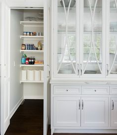 Chic white kitchen features a freestanding glass front china cabinet placed next to a walk-in pantry lined with floating shelves.