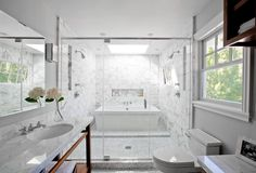 Bathroom with a freestanding tub inside a glass enclosed marble shower, white vein-y Carrara marble tiles, wood vanity with marble top, a skylight and chrome fixtures
