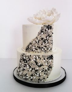 two-tiered cake with black, silver and white pearl accents