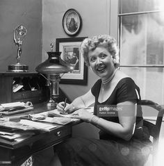 American actor Vivian Vance (1907 - 1979), best known as Ethel Mertz of television's 'I Love Lucy,' smiling and looking to the side as she writes letters at her home desk.