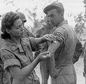 U.S. Army nurse instructs Army medics on the proper method of giving an injection, Queensland, Australia, 1942. (DA photograph)