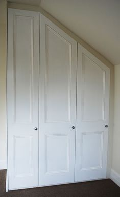 built-in closets next to a sloped ceiling