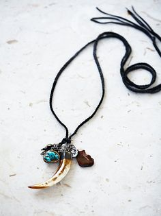 Kuraka Leather Necklace | Hand made vintage-inspired leather necklace featuring brown agate, Tibetan turquoise and bone horn drops with hand carved white bronze charms. Adjustable tie closure.