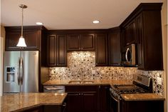 Kitchen design idea that has beautiful black cabinets and a unqieu tile backsplash