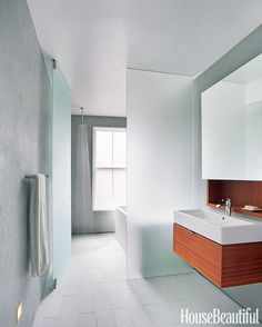 A plane of frosted glass separates the wet side of the bathroom, with the open shower, from the dry side, with the sink.