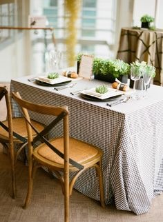 Gingham table cloth, wooden chairs, and succulent centerpieces