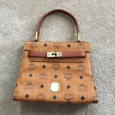 """MCM Handbag Authentic Vintage MCM Handbag. A really small handbag but the quality is phenomenal!!! Unlike the more recent MCM's sold. The monogram doesn't fade.  Width 9"""" Length 7"""" side width 3 1/8 handle drop 5"""" had this baby for years because it's true quality!! MCM Bags"""